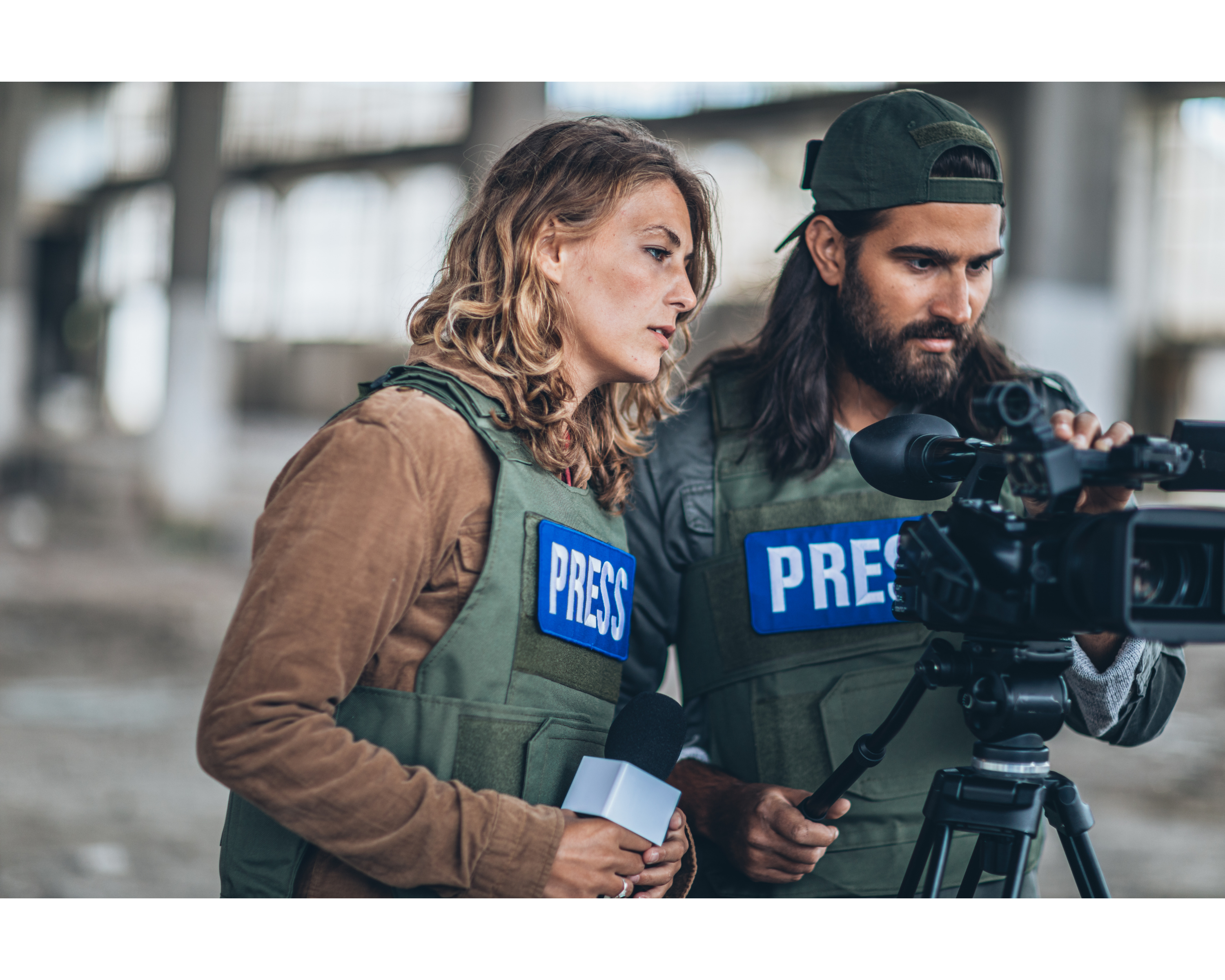 Two journalists prepare a broadcast from the street wearing vests that say Press.