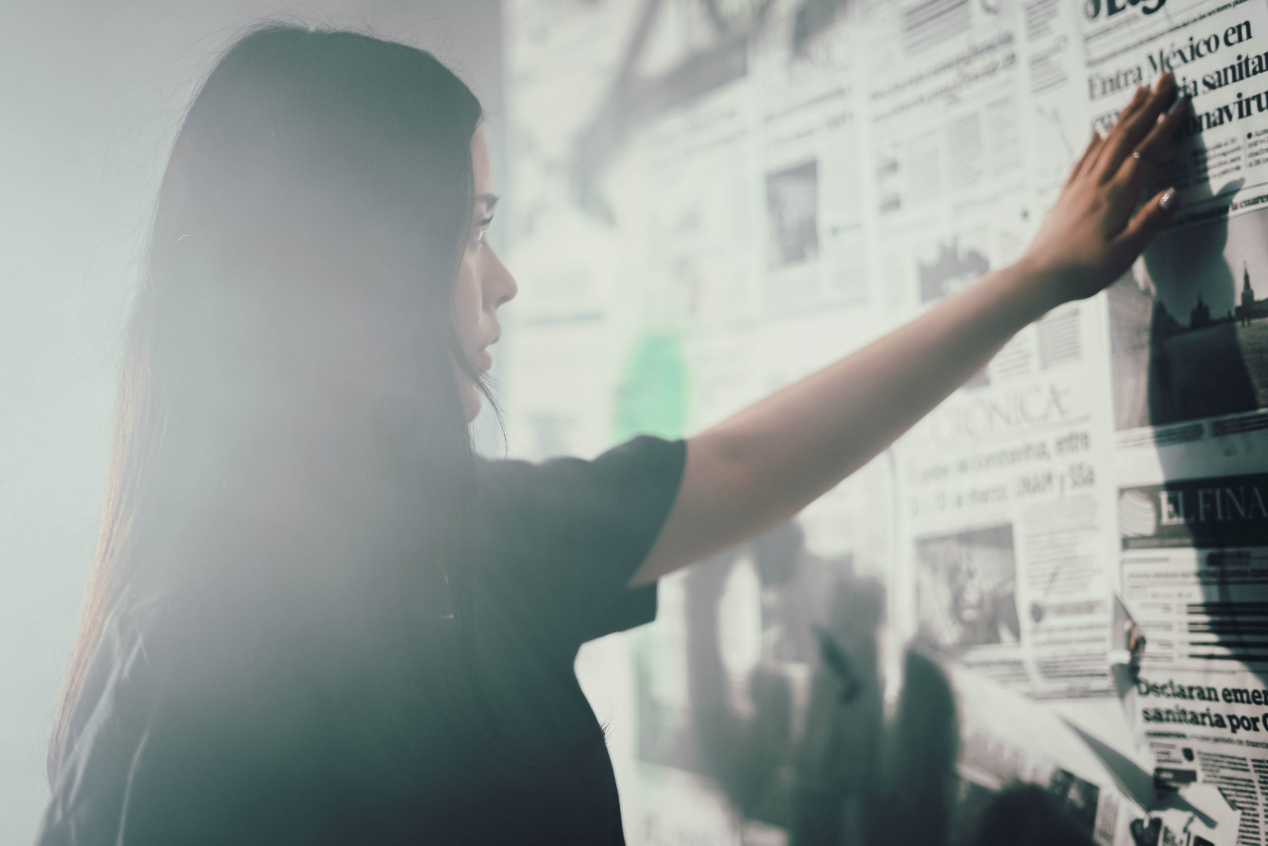 A woman stands in front of a wall of newspapers.